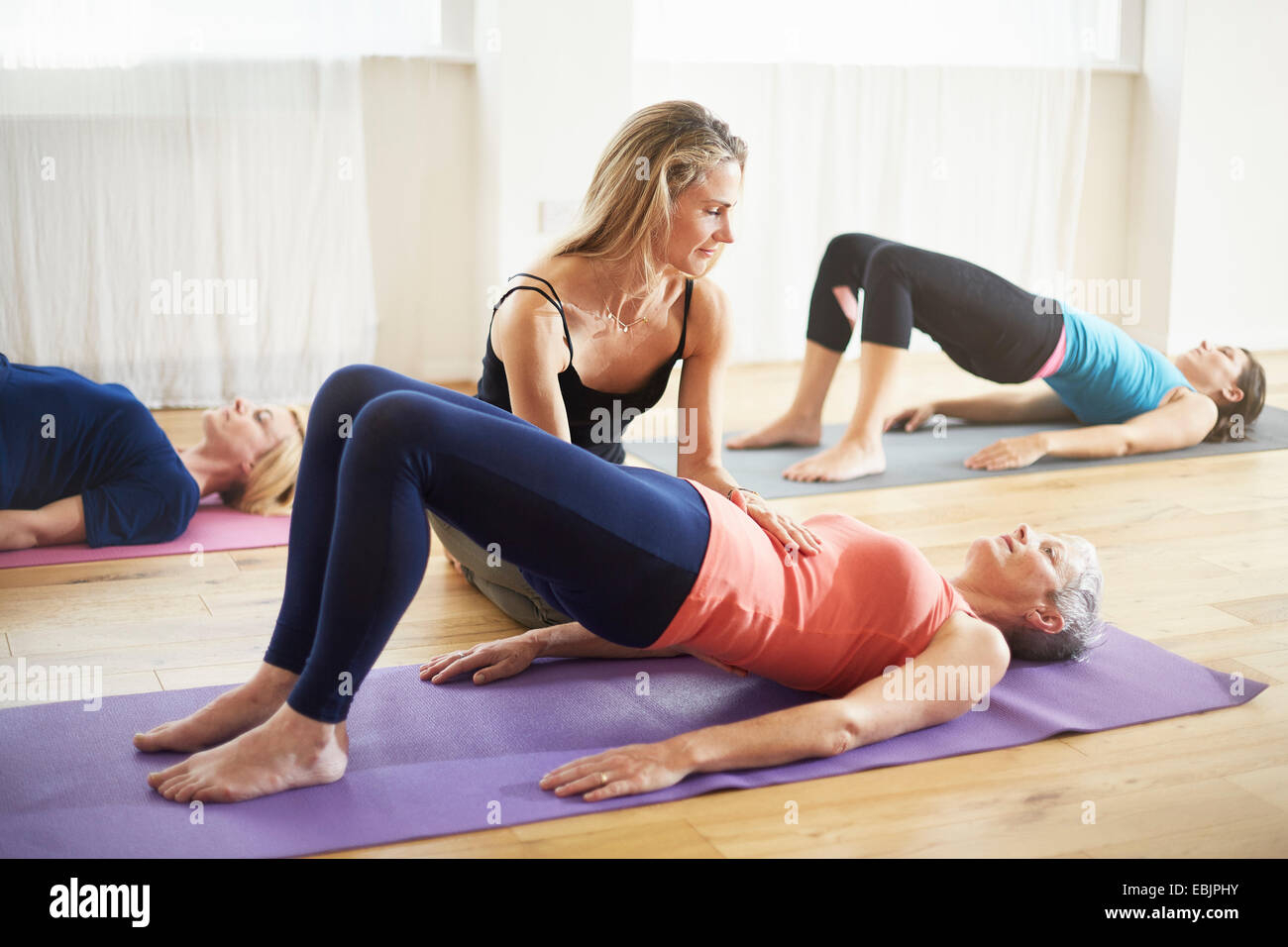 Unterricht, die Schüler auf Rücken in Pilates-Klasse zu unterstützen Stockbild