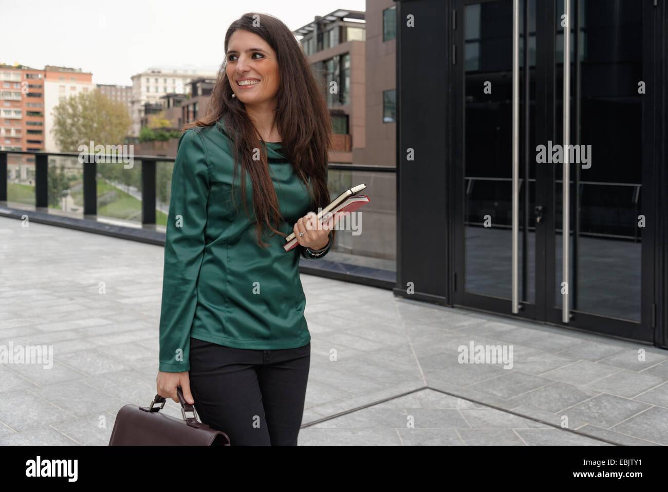 Junge berufstätige Frau zu Fuß mit dem Aktenkoffer Stockbild