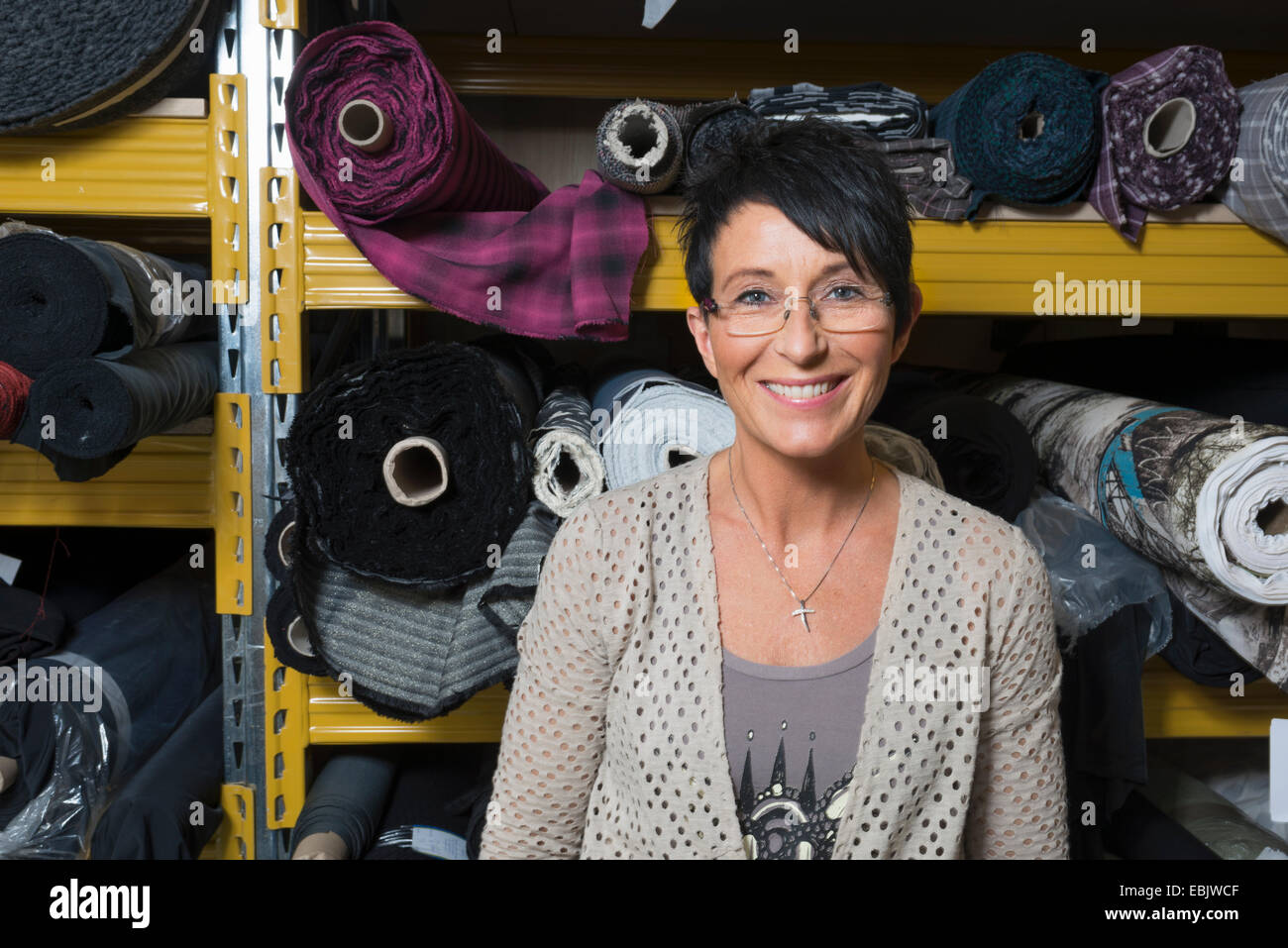 Porträt von Reifen Näherin vor Rollen Textil in Werkstatt Stockbild