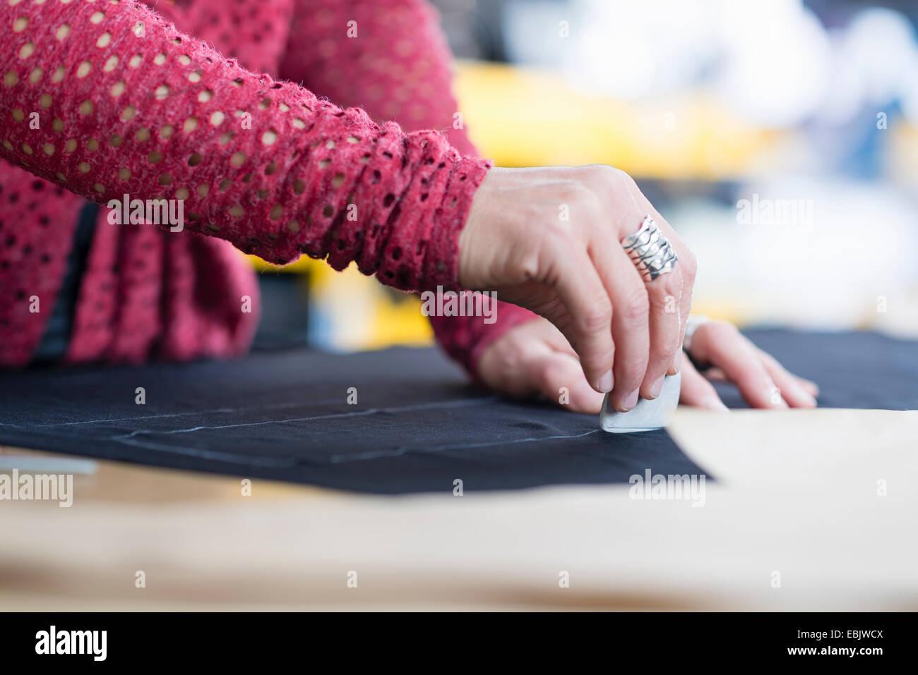 Händen der Reife Näherin Kreidung Umriss auf Textil auf Arbeitstisch Stockbild