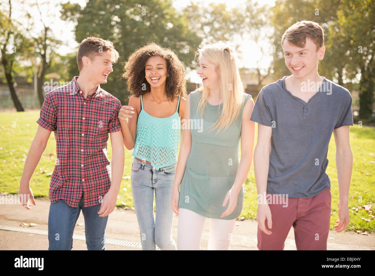 Vier junge Erwachsene Freunde, die einen Spaziergang im park Stockbild