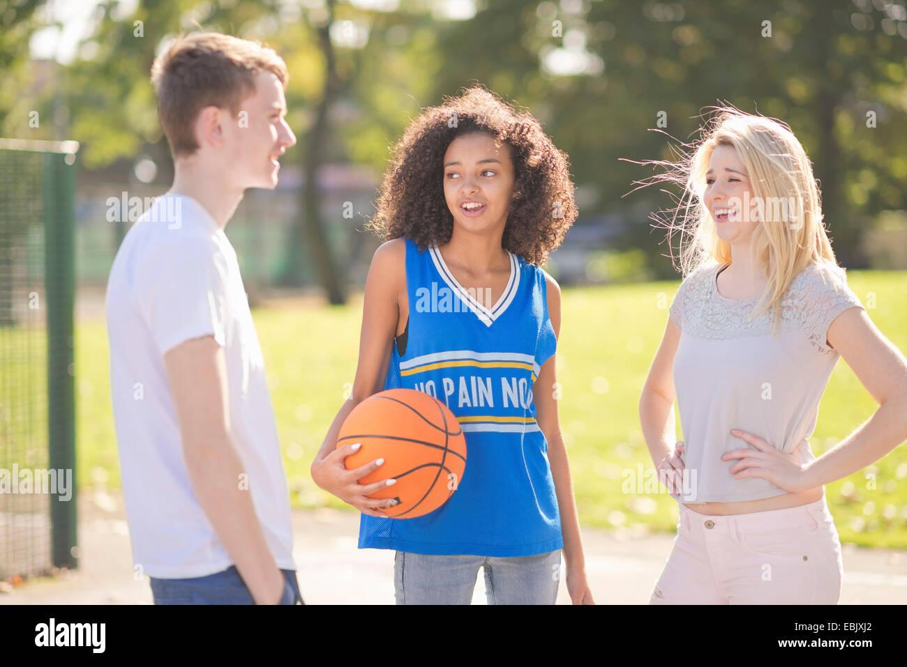 Drei junge Erwachsene Basketball-Spieler im Chat Stockbild