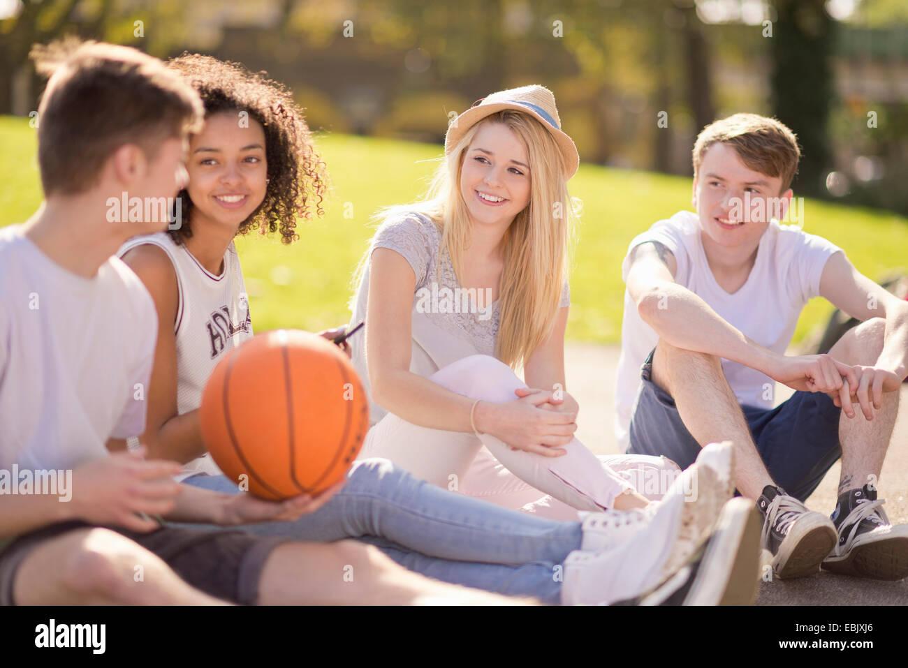 Vier junge Erwachsene Basketball-Spieler sitzen im Chat Stockbild