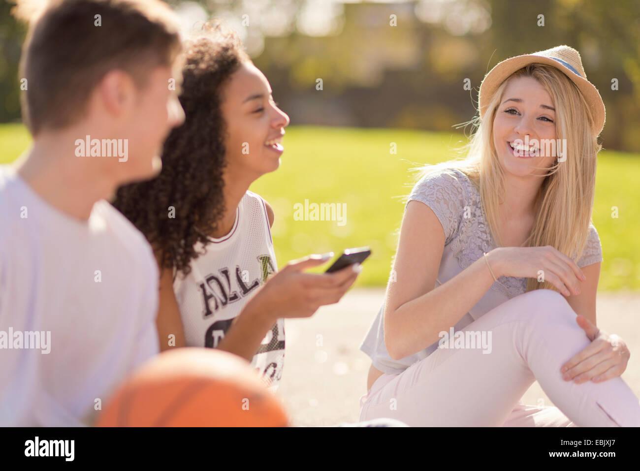 Drei junge Erwachsene Basketball-Spieler, plaudern und lachen Stockbild