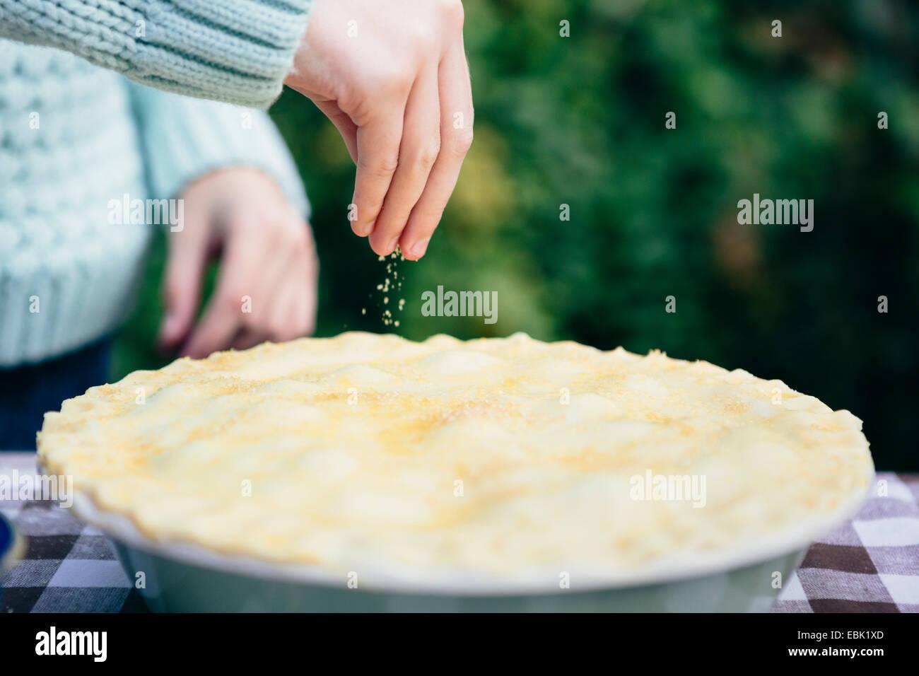 Mädchen, die Prise Zucker auf hausgemachte Kuchen Stockbild
