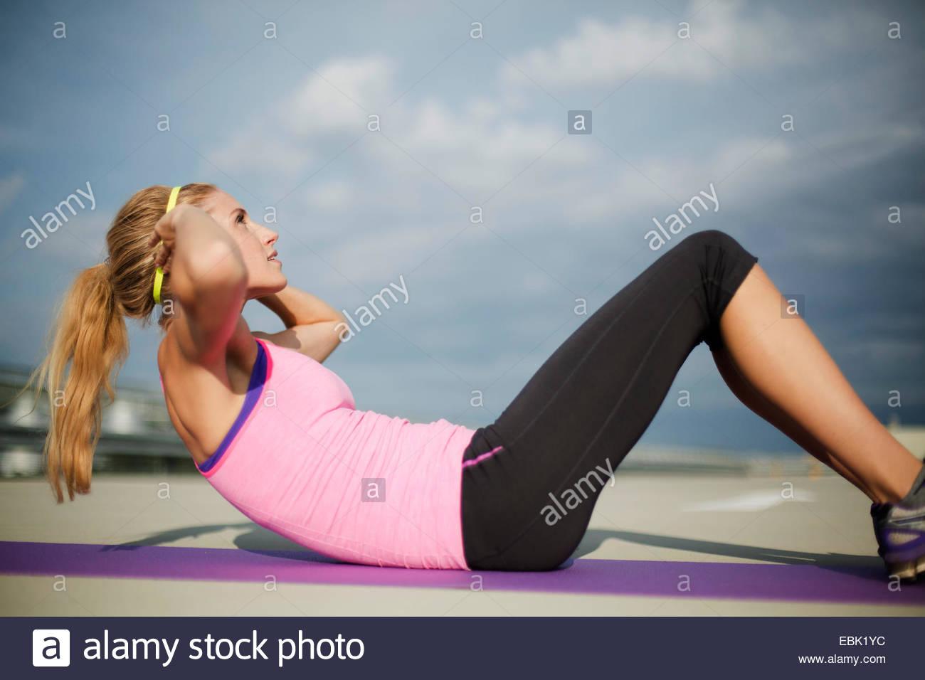 Junge Frau dabei Sit Ups Stockfoto