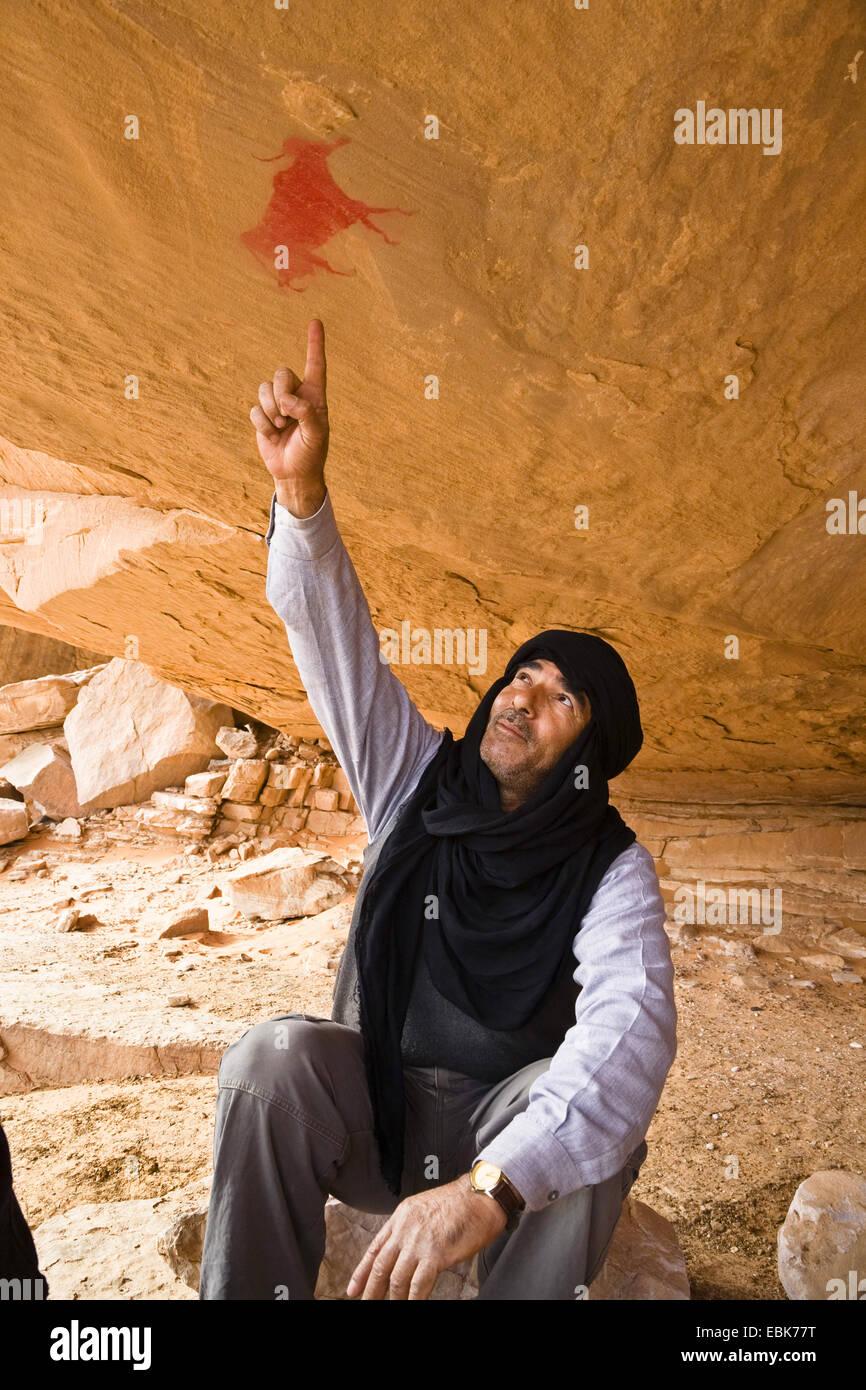 Touareg sitzen unter einem Felsvorsprung auf prähistorischen Felsmalereien im Acacus Berge, Libyen, Sahara Stockbild