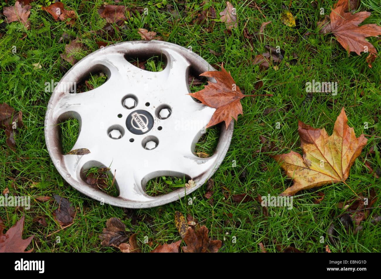 Eine verlorene Radkappe auf einer Kante am Straßenrand liegen. Stockbild