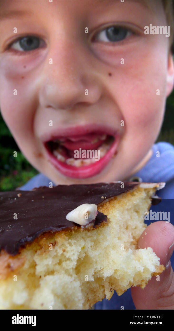 Junge hat ein Milchzahn einen Kuchen essen verloren. Stockbild