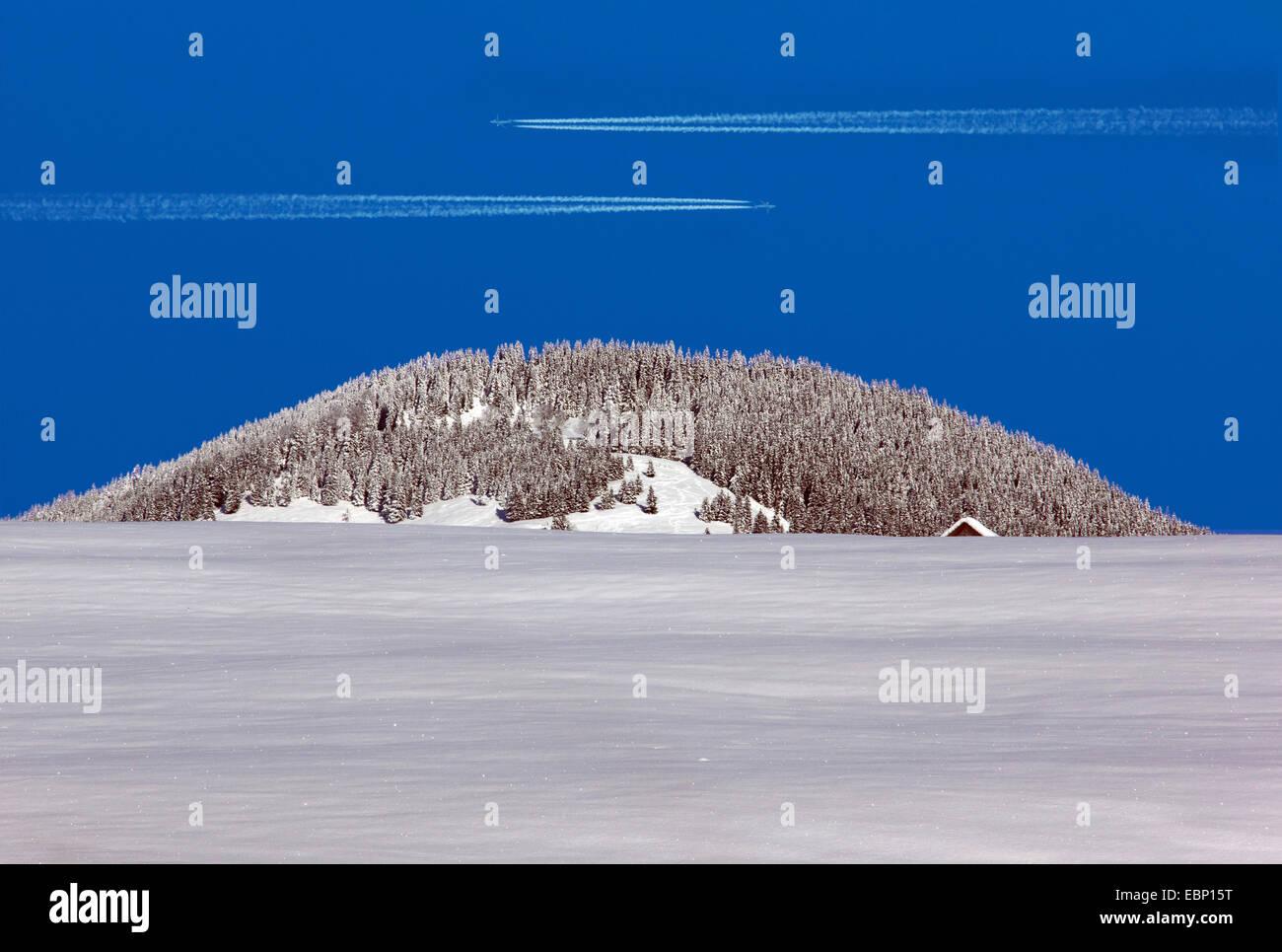 zwei Vapor Trails von Flugzeugen im blauen Himmel über dem Hoernle Gipfel im Winter, Deutschland, Bayern, Oberbayern, Stockbild