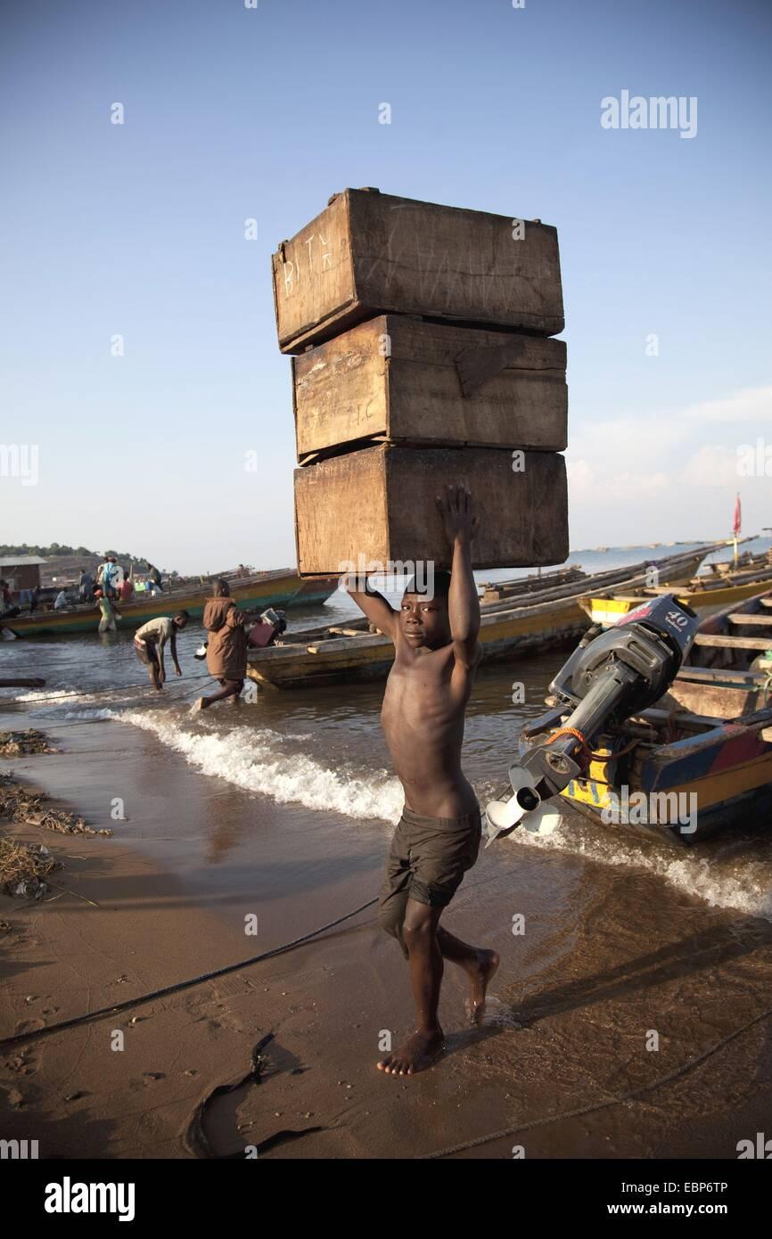 Junge mit drei Holzkisten gestapelt auf dem Kopf mit kurzem gefangen Fisch vom Boot zum Ufer von wo es in die Hauptstadt, Stockbild