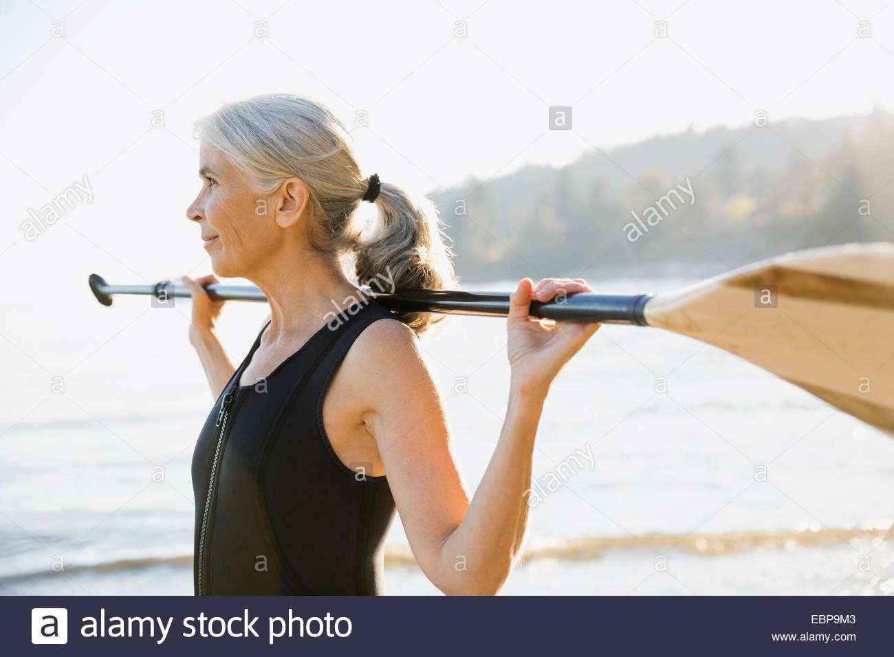 Ältere Frau mit Paddel am Sonnenstrand Stockbild