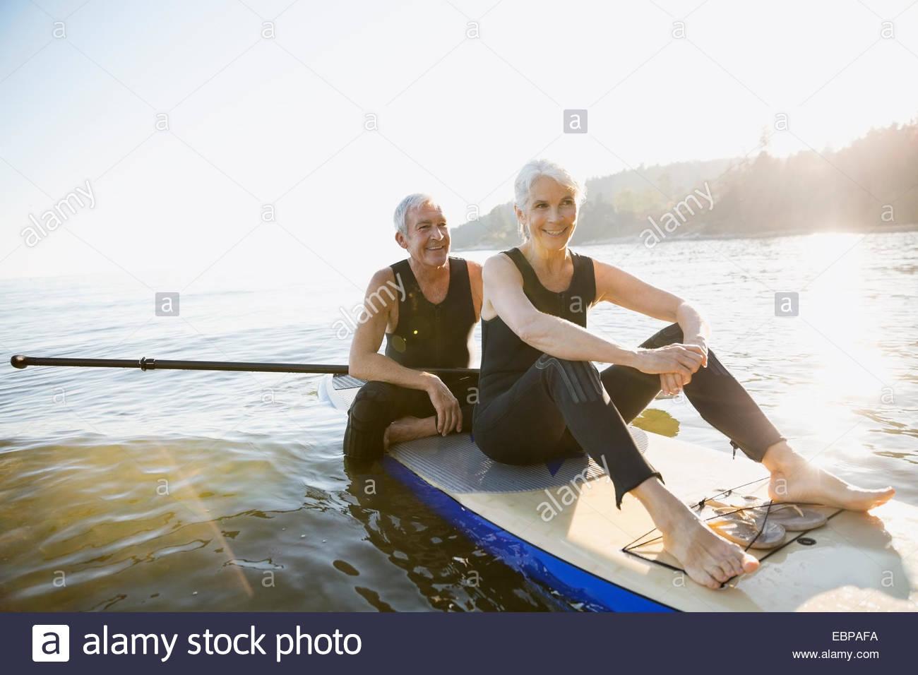 Älteres Paar Paddel Board im Ozean Stockbild