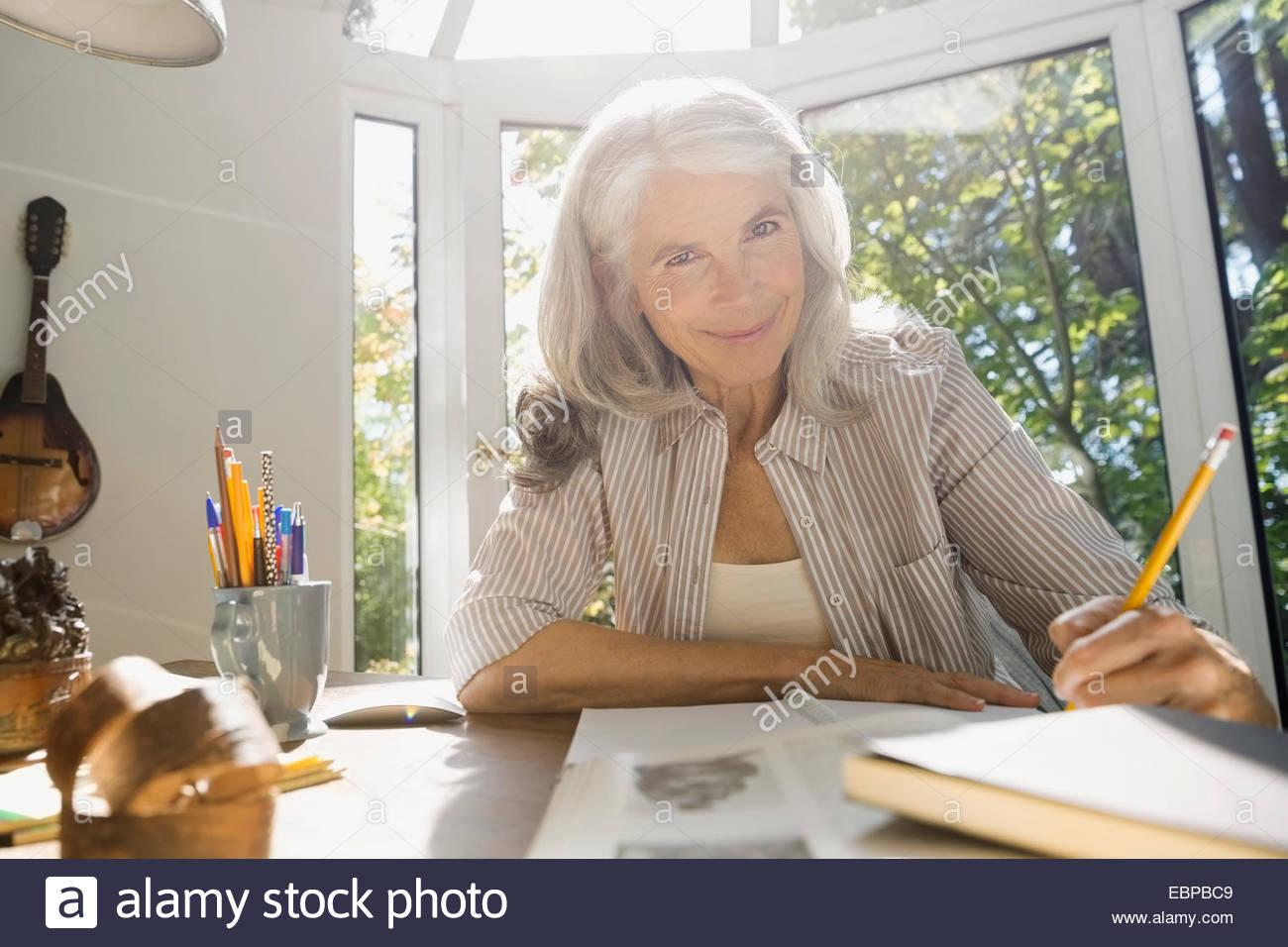 Porträt von senior Frau schreiben im home-office Stockbild