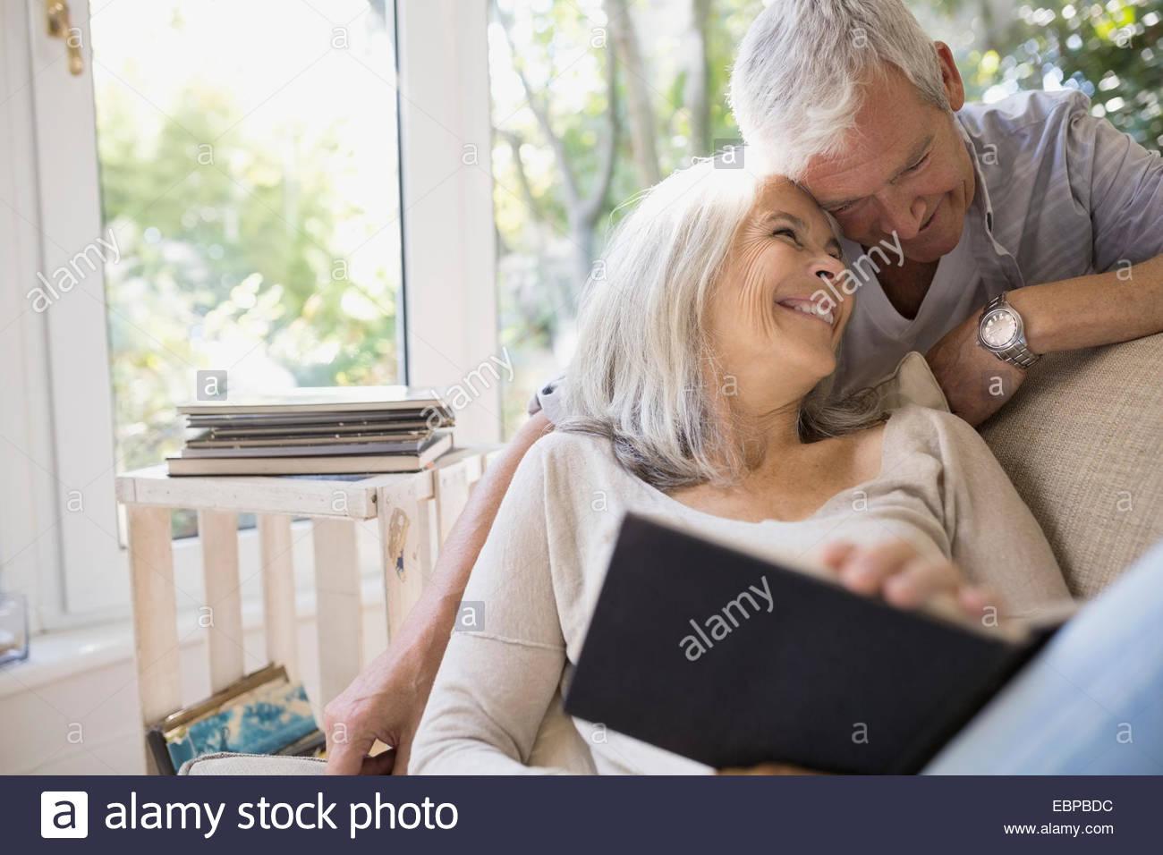 Älteres paar umarmt im Wohnzimmer Stockbild