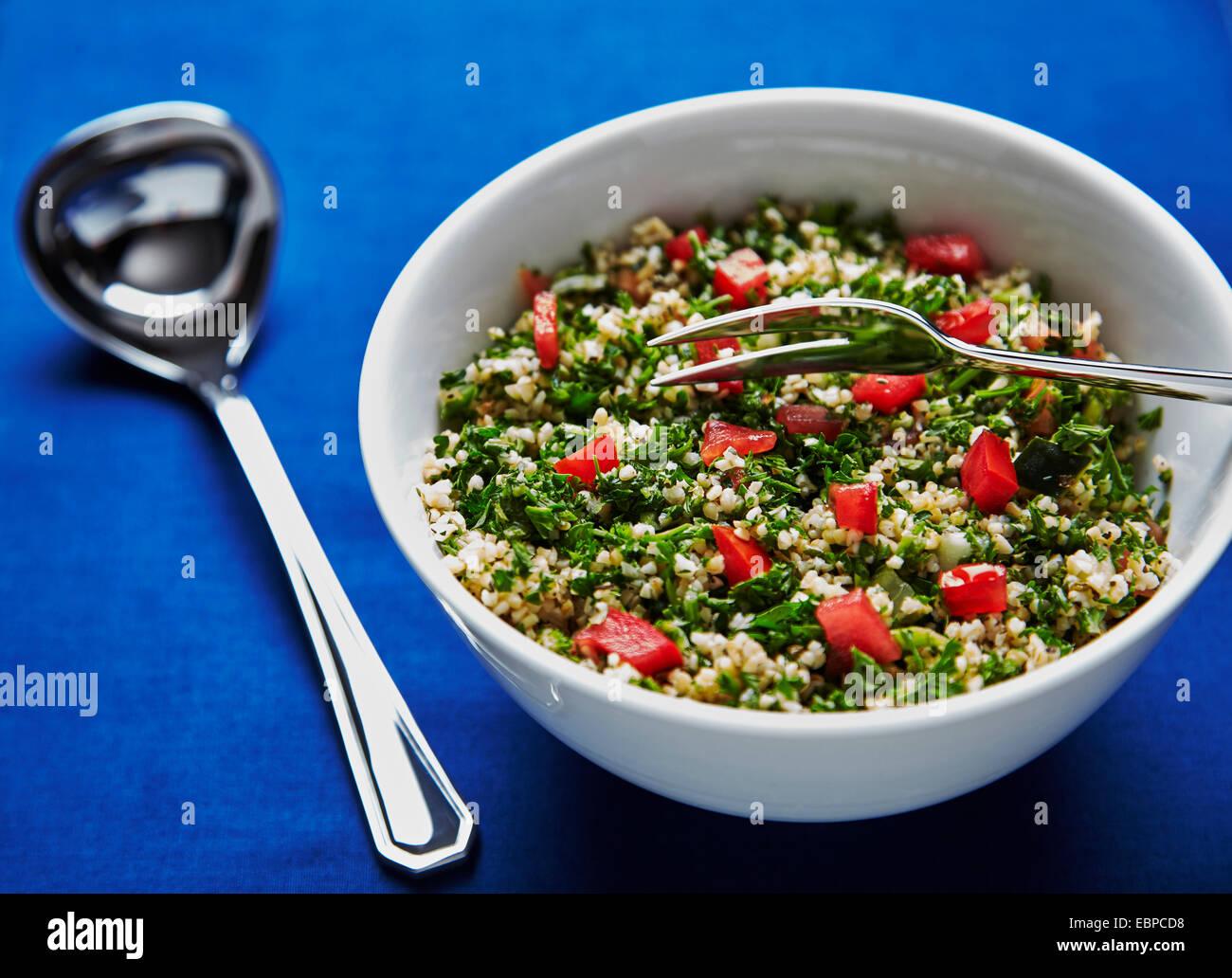 Taboulé Salat in einer weißen Schüssel auf einem dunkelblauen Hintergrund mit silbernen Löffel und einer Gabel serviert Stockfoto