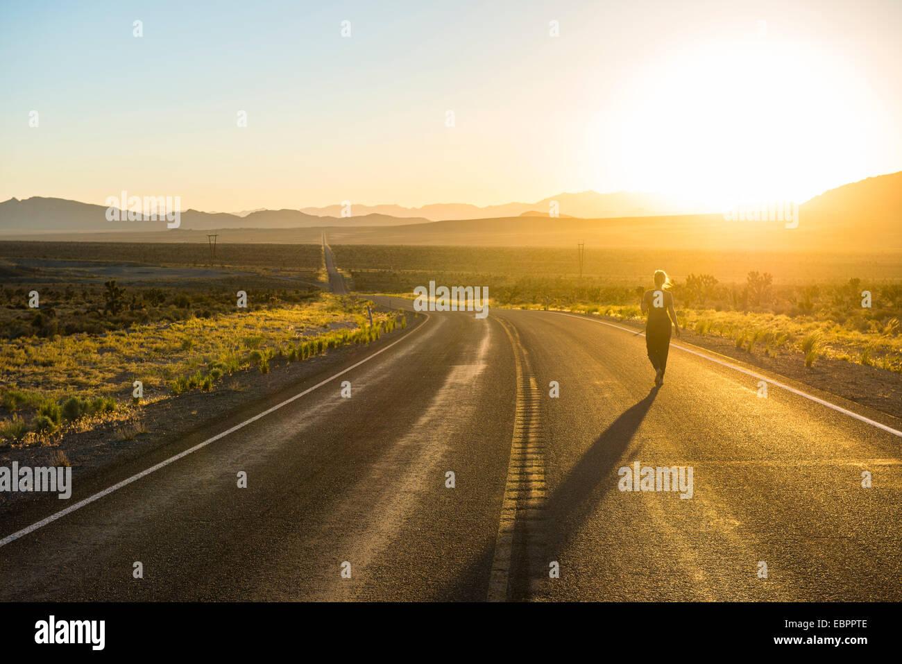 Frau zu Fuß hinunter eine lange kurvenreiche Straße bei Sonnenuntergang im östlichen Nevada, Vereinigte Stockbild