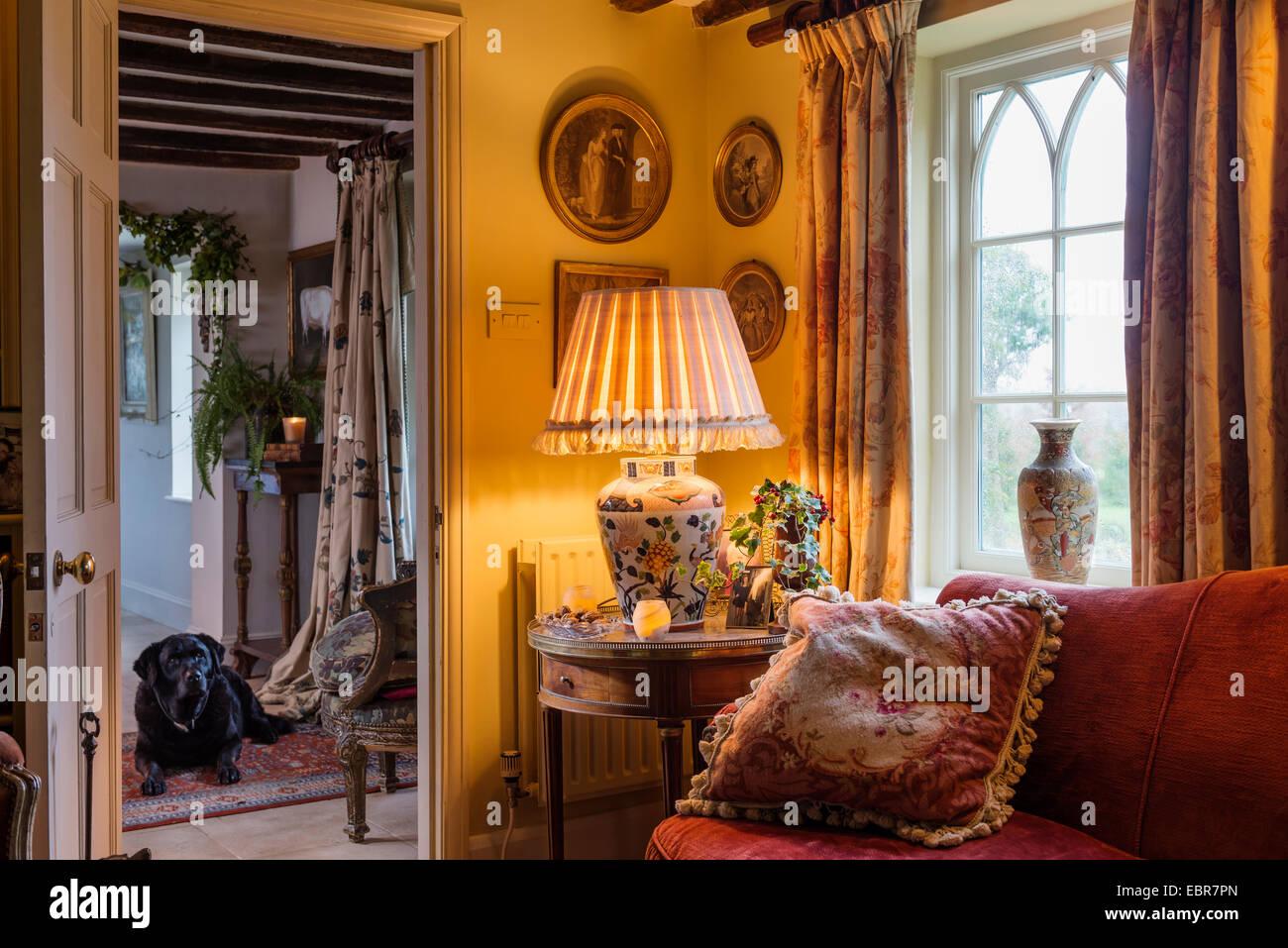 Gobelin Kissen auf roten Sofa im Wohnzimmer mit floral Gardinen und ...