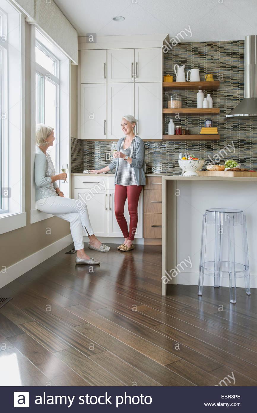 Frauen, Wein trinken und reden in Küche Stockbild