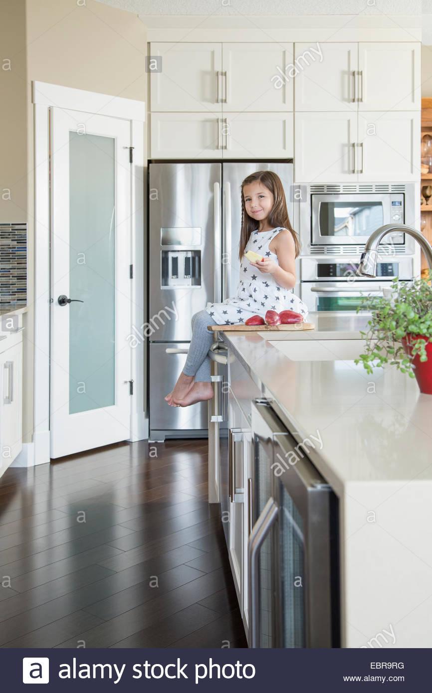 Porträt von lächelndes Mädchen Essen auf Kücheninsel Stockfoto, Bild ...