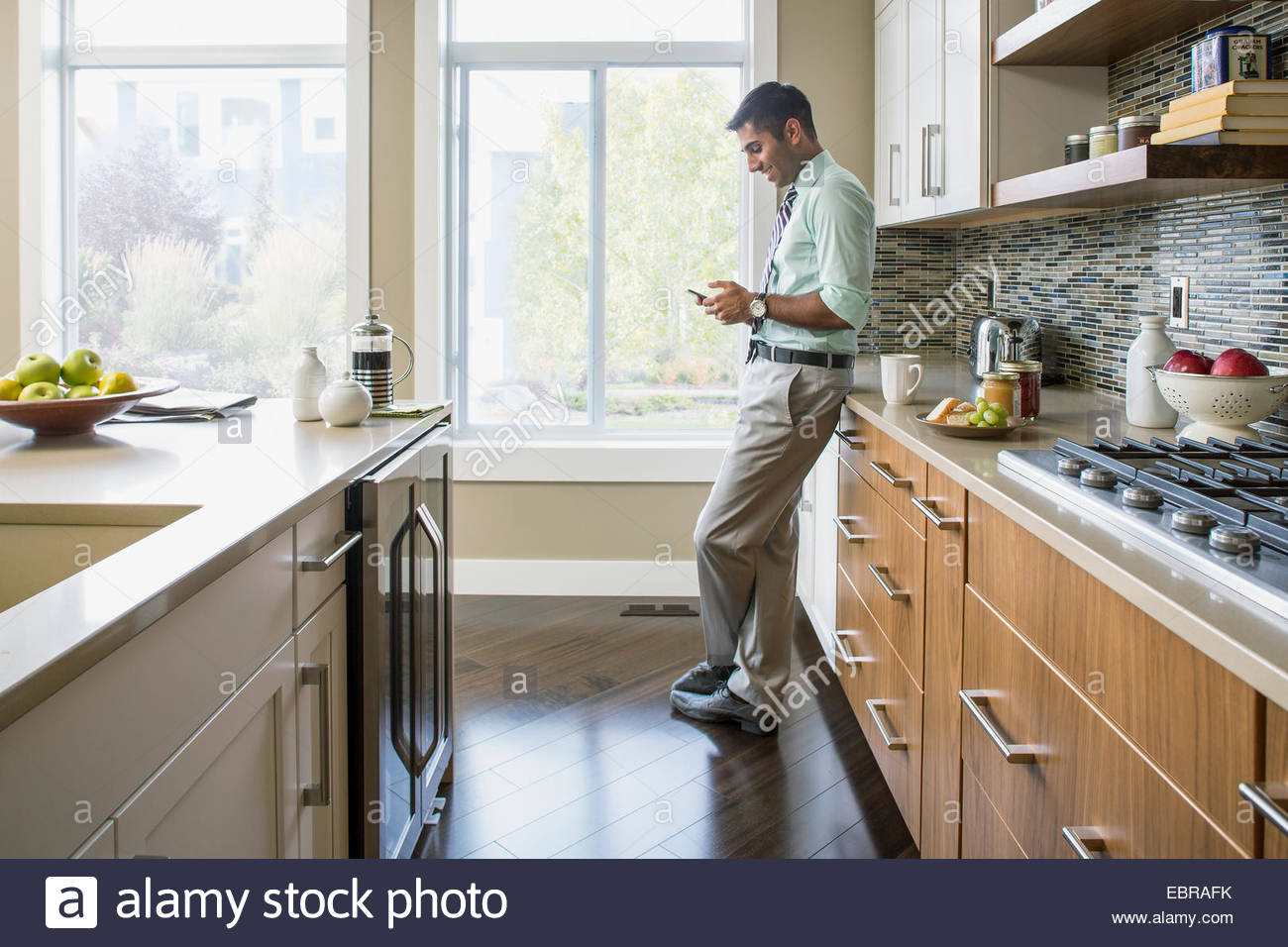Mann-SMS auf Handy in Küche Stockbild
