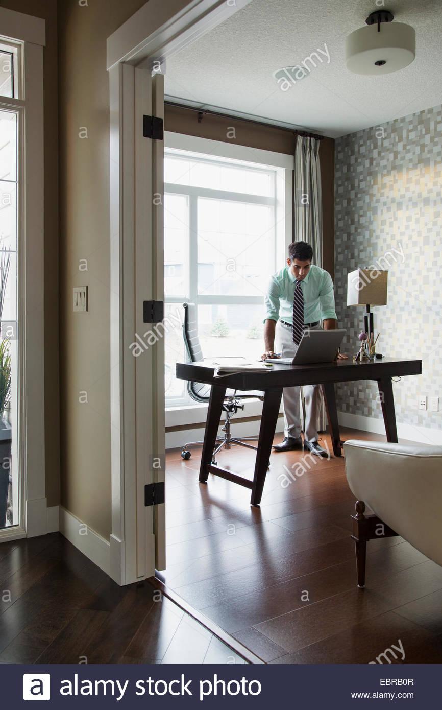 Mann mit Laptop im home-office Stockbild
