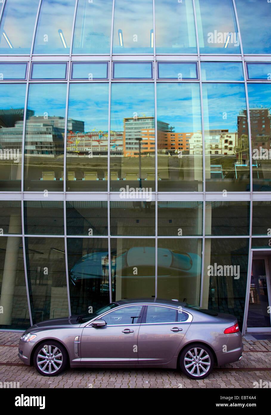 """ein Auto vor """"Haus Vor Dem Wind"""", Medienhafen, die Spiegelung in der Glasfassade, Deutschland, Nordrhein Stockbild"""