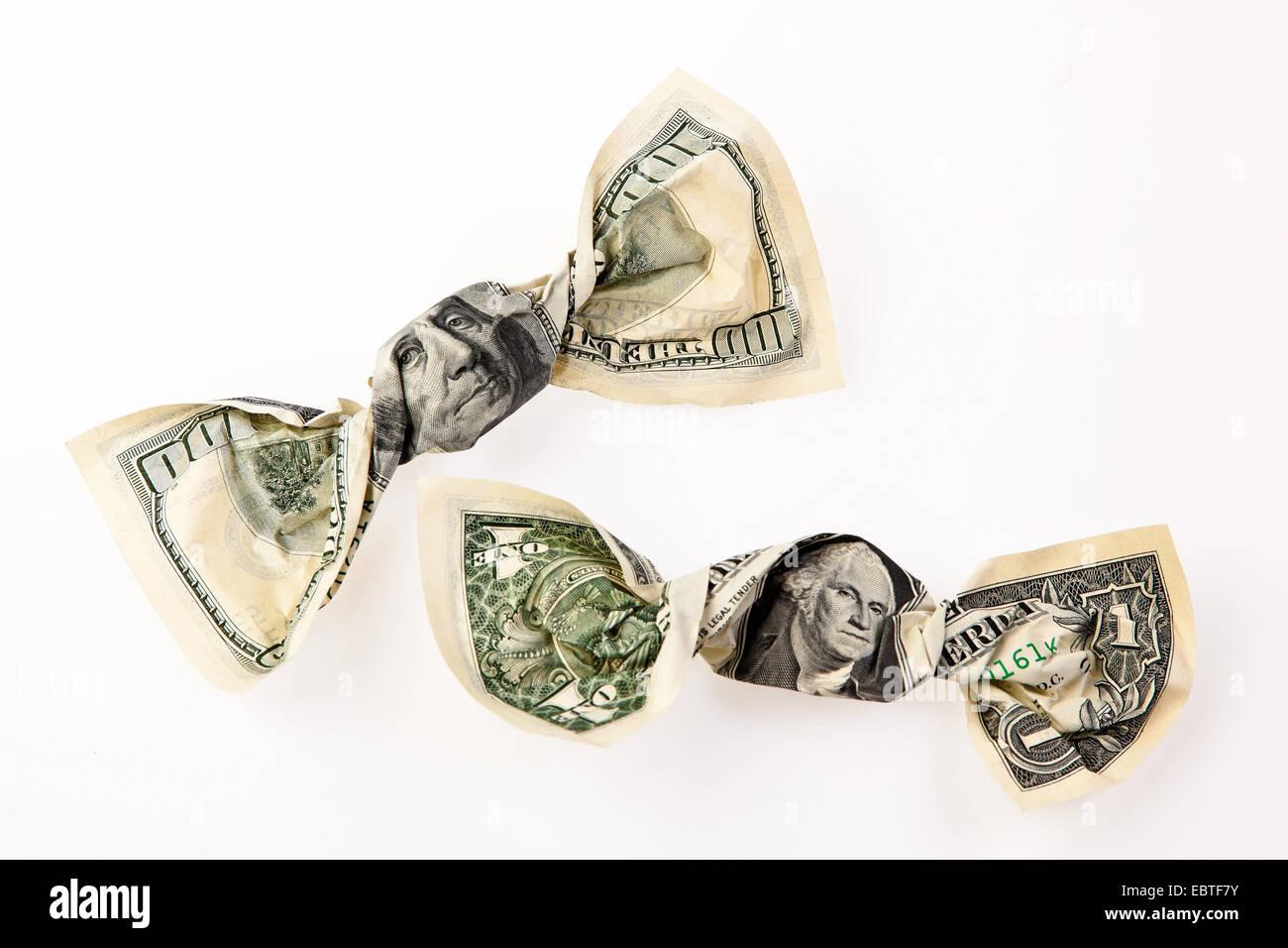 Bonbons eingewickelt in Dollarnoten als Symbol für die Reduzierung von Steuern als Versprechen während Stockbild