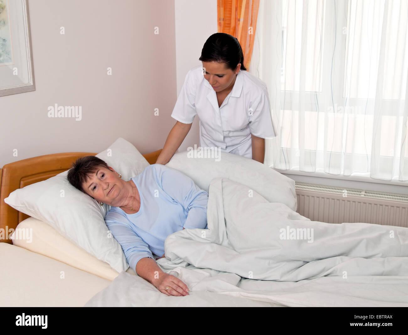 krankenschwester f r ltere menschen ist die sorge um eine bettl gerige ltere frau stockfoto. Black Bedroom Furniture Sets. Home Design Ideas