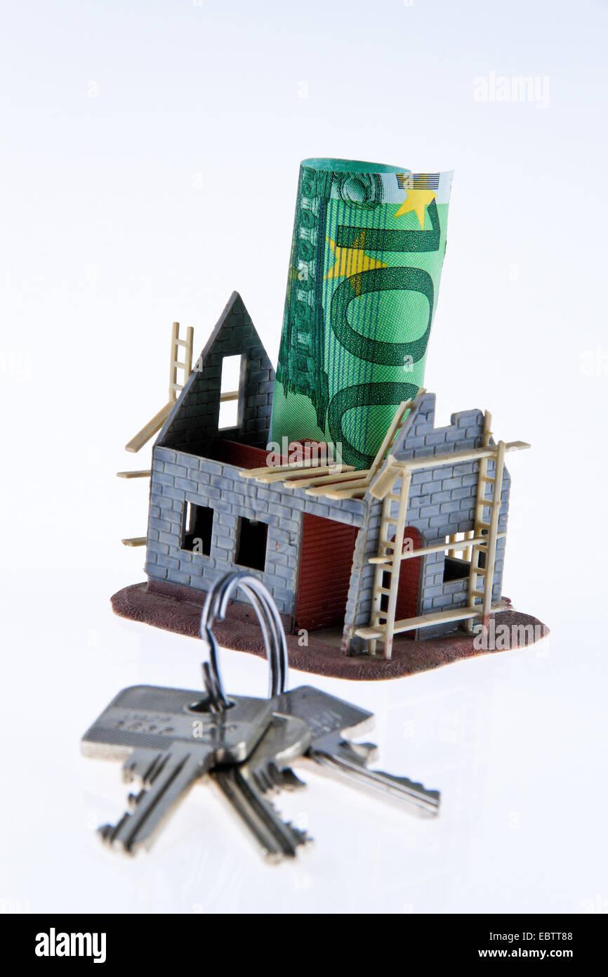 """Symbolbild """"Wohnungsbau und Finanzierung"""": Euro-Scheine stecken in dem Modell der Rohbau eines Hauses Stockbild"""