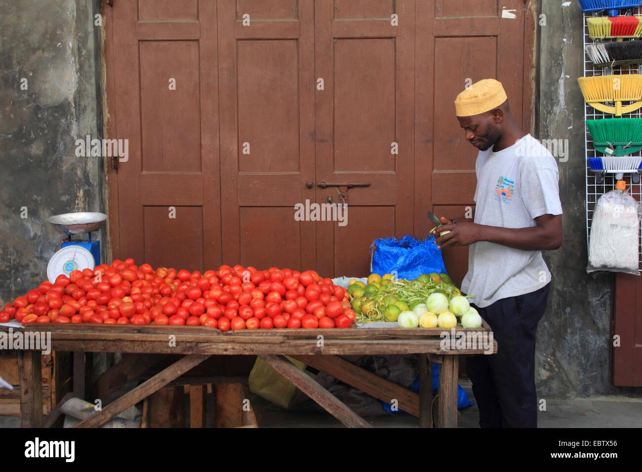 dunkelhäutigen Mann Tomaten, Tansania, Sansibar, Stone Town zu verkaufen Stockbild