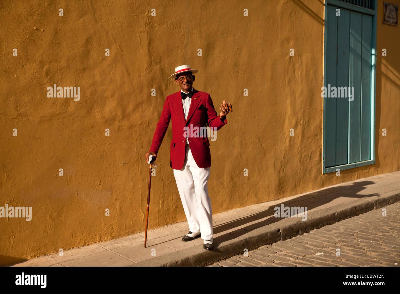 Schauspieler Pedro Pablo Perez trägt einen roten Anzug mit einem Hut und einer Zigarre, Havanna, Kuba Stockbild