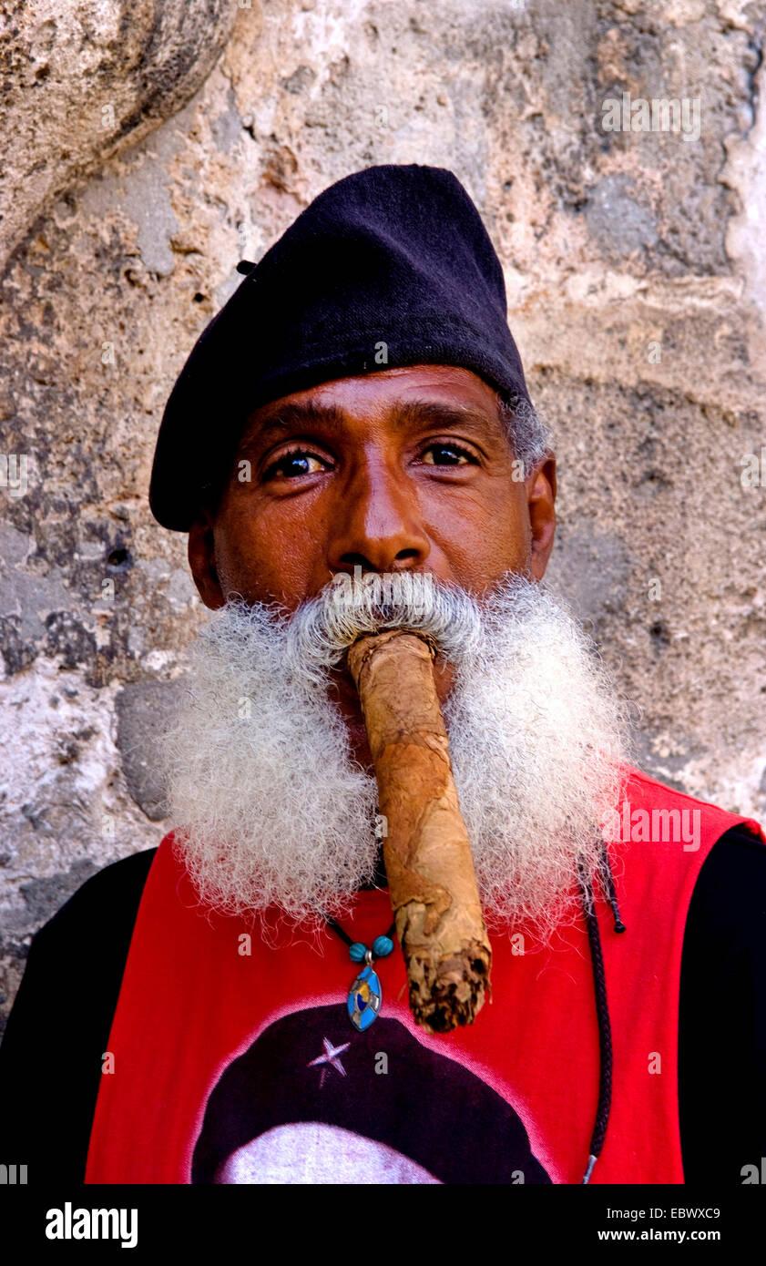 Mann mit Vollbart und Baskenmütze eine lange Zigarre rauchend, Kuba, La Habana Stockbild