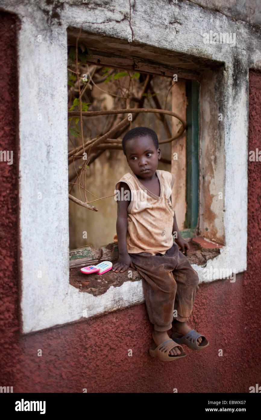 kleiner Junge sitzt in einem Fensterrahmen Krieg zerstörten Hauses, Burundi, Karuzi, Buhiga Stockbild