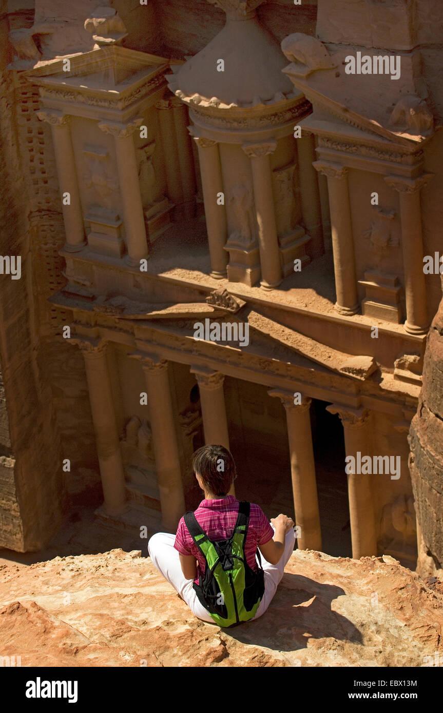 junge Backpacker sitzt auf einem Felsvorsprung mit Blick auf die Veranda des Felsens schneiden Grab genannt 'Fiskus' Stockbild