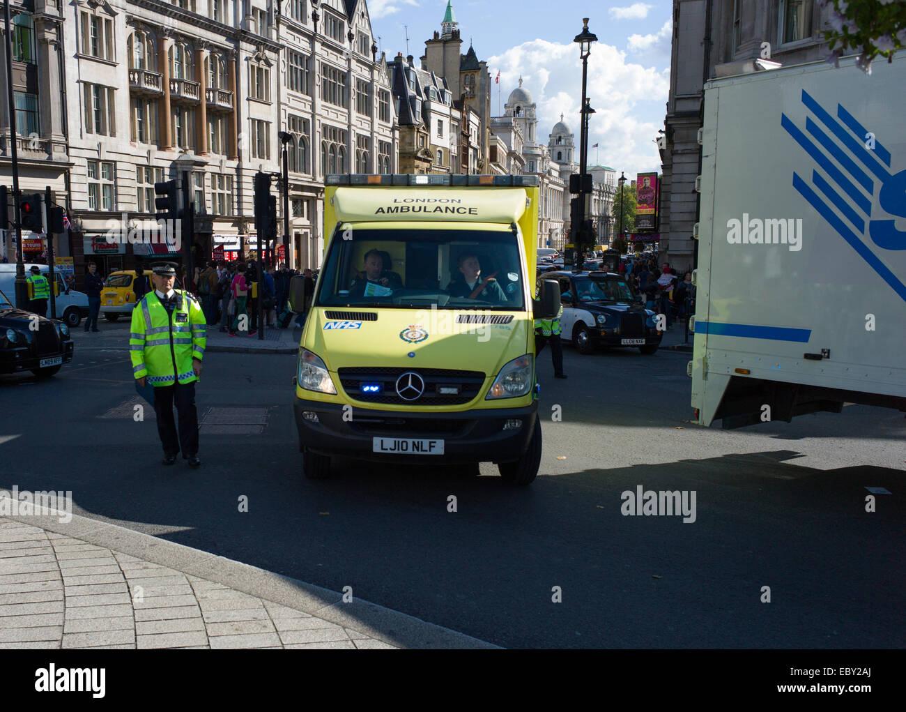 Ein londoner Krankenwagen ist durch den Verkehr von der Polizei in der Nähe von Trafalgar Square half Stockbild