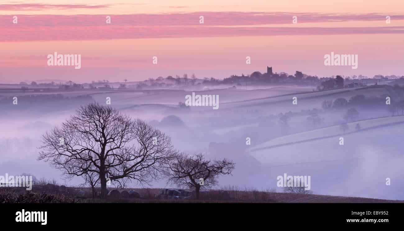 Nebel verhüllte Landschaft mit Blick auf das Dorf von Morchard Bischof, Devon, England. Winter (März) 2014. Stockfoto