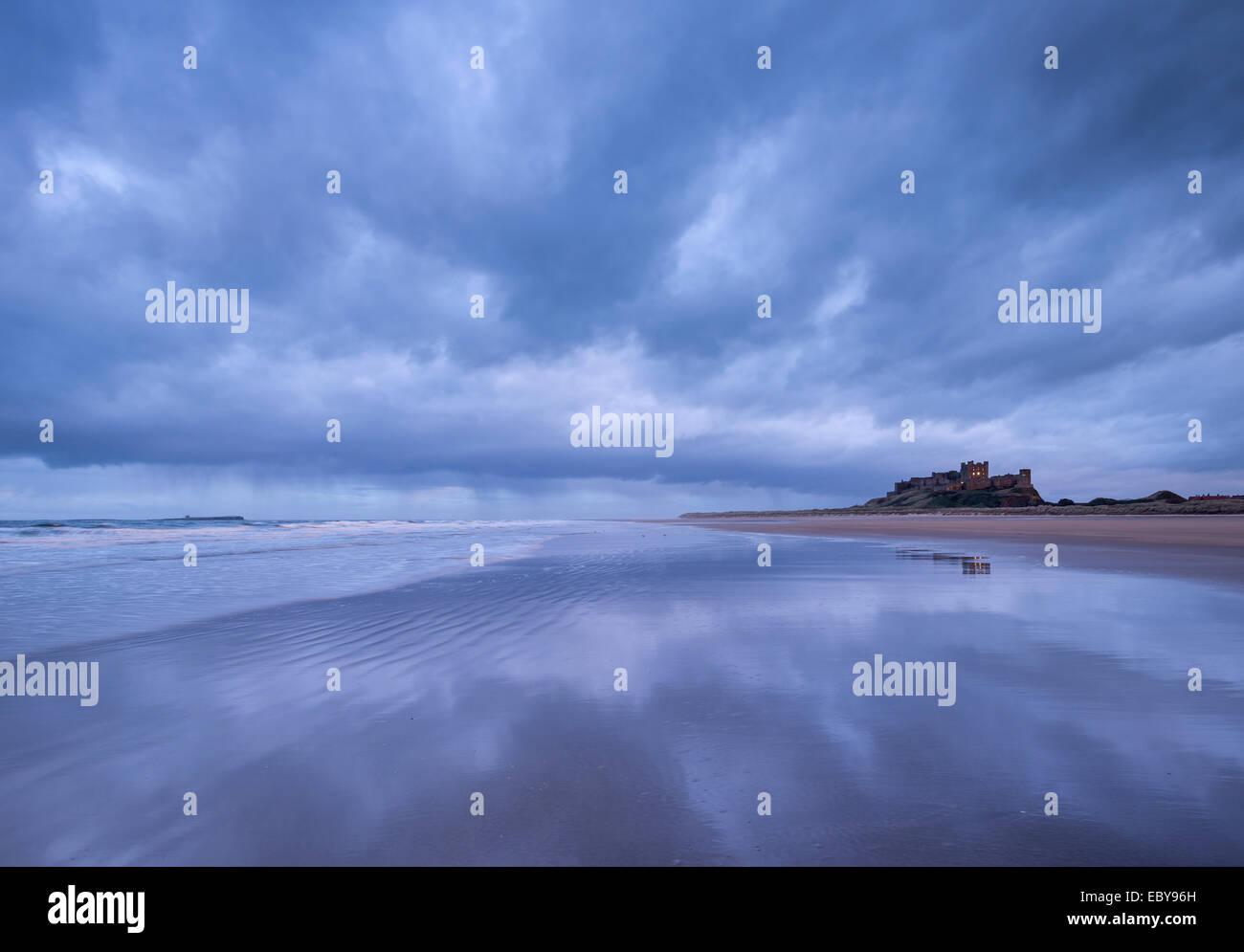 Sturmwolken reflektieren am menschenleeren Strand neben Bamburgh Castle in Northumberland, England. Winter (März) Stockbild