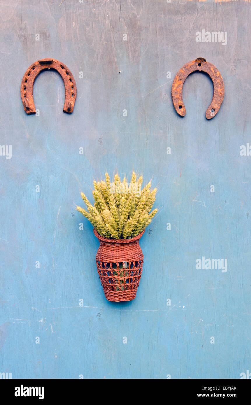 zwei Hufeisen Glückssymbol und Korb mit Ähren auf blauen alten Bauernhof-Wand Stockbild