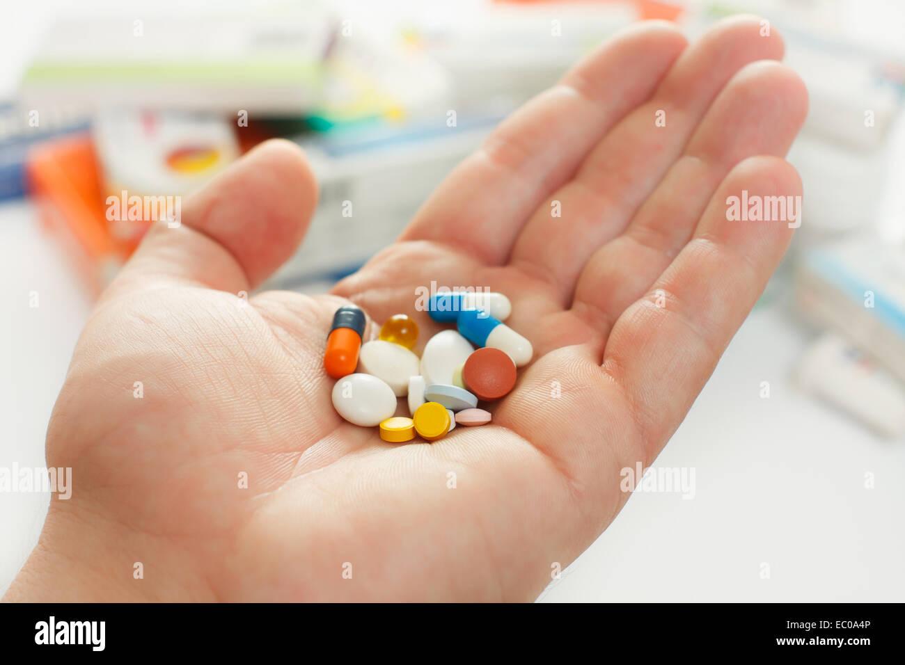 Hand des Mannes halten viele Arzneimittel, Boxen von Arzneimitteln im Hintergrund Stockbild