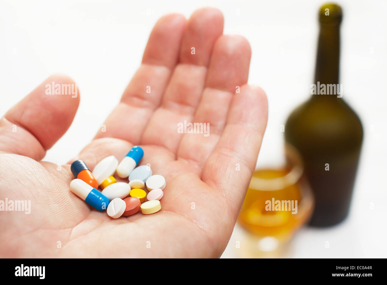 Hand des Mannes halten viele Arzneimittel. Flasche und Glas mit Alkohol im Hintergrund Stockbild