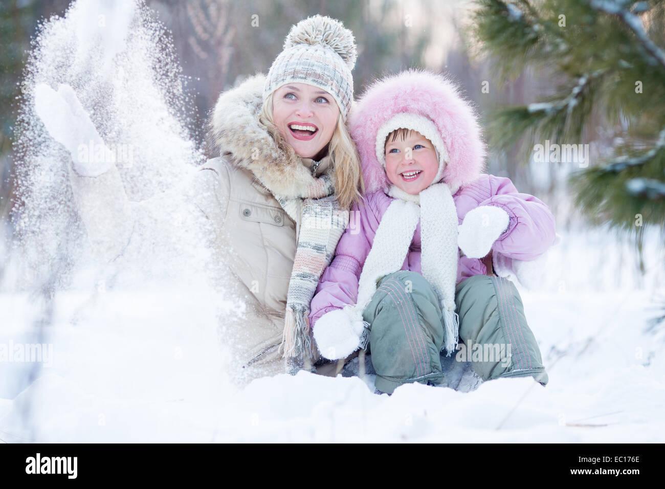 Glückliche Eltern und Kind spielt mit Schnee im Winter im freien Stockbild