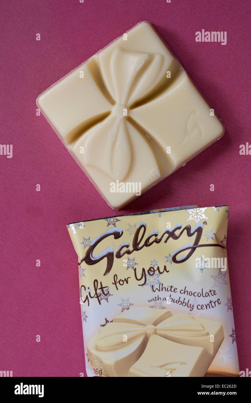 Galaxy-Geschenk für Sie weiße Schokolade mit einem sprudelnden Zentrum entfernt vom Wrapper auf rosa Hintergrund Stockbild