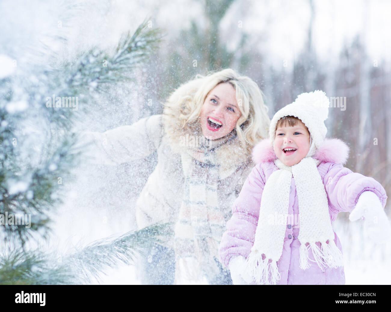 Glücklich Mopther und Kind spielt mit Schnee im Winter im freien Stockbild