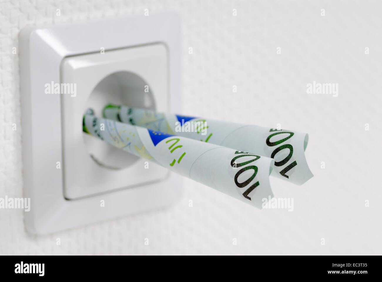 Steckdose mit Euro-Banknoten, Energiekosten Stockbild