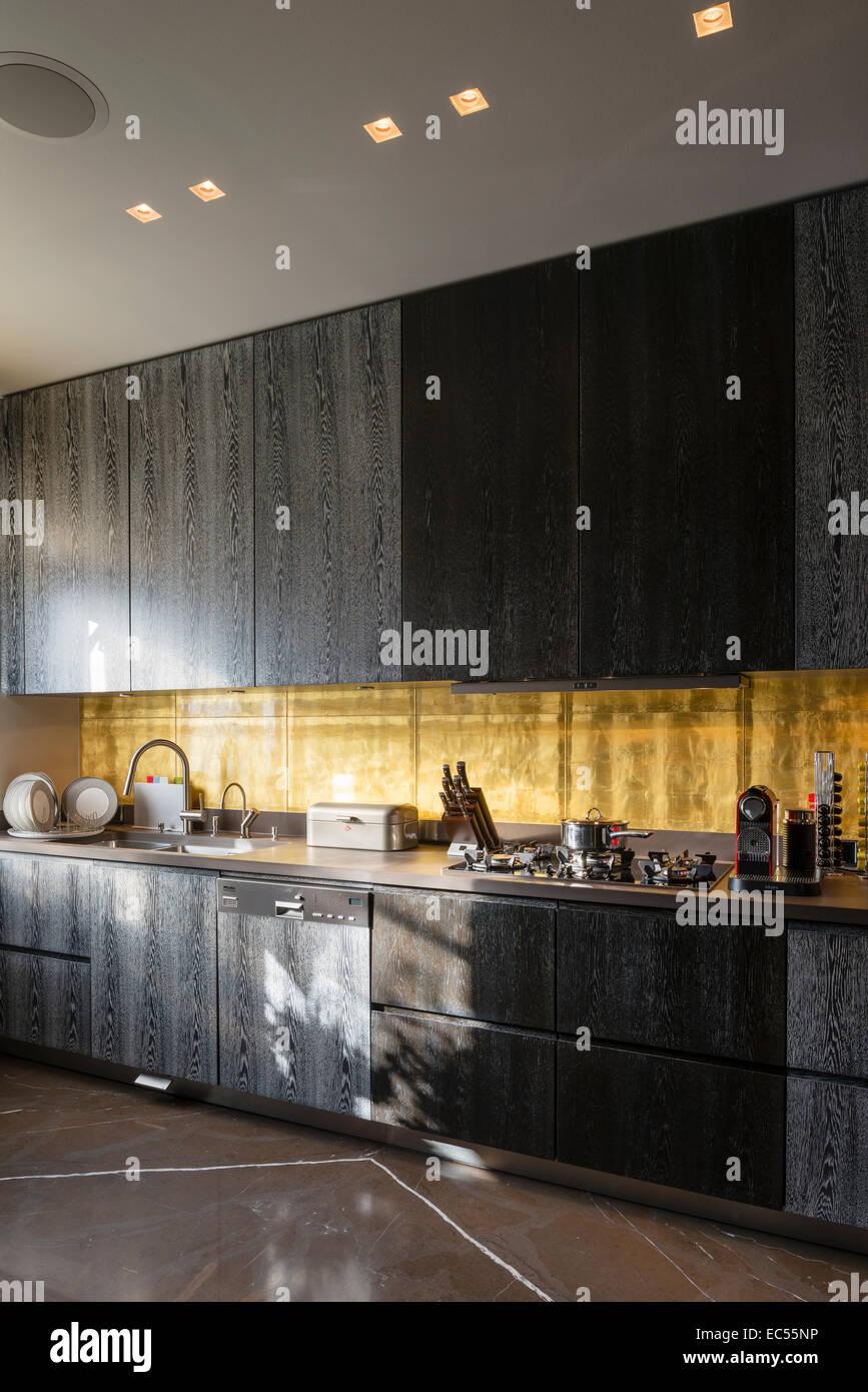 Blattgold Backsplash In Küche Mit Dunklen Rauchigen Eiche Schränke Stockbild
