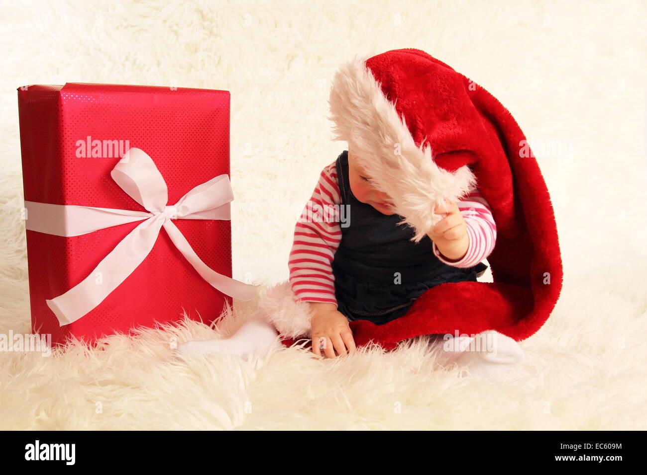 Ein Baby darüber hinaus eine Weihnachtsmann-Mütze und ein Geschenk Stockbild