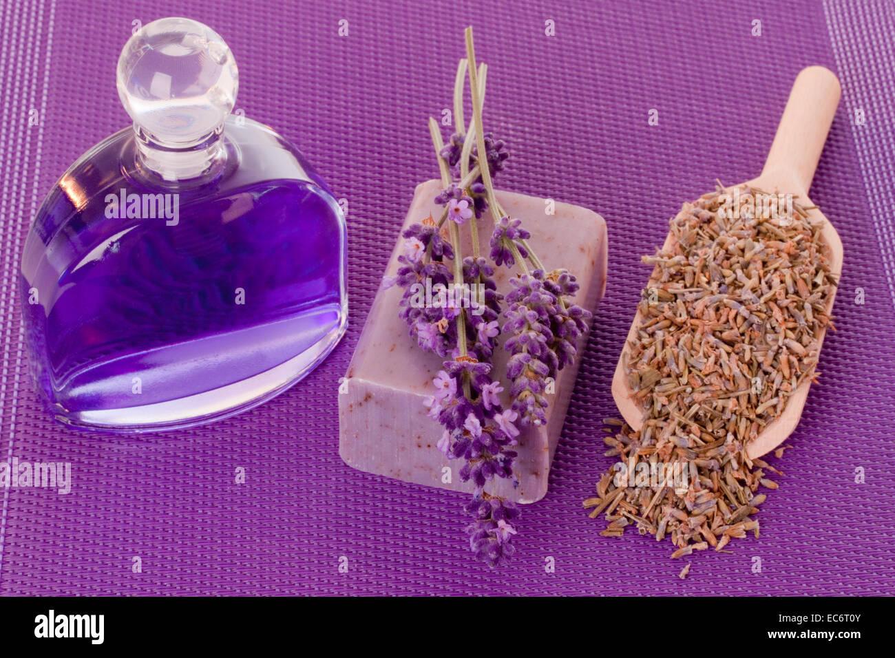 Badezusatz und Seife mit Lavendel auf lila Hintergrund Stockbild