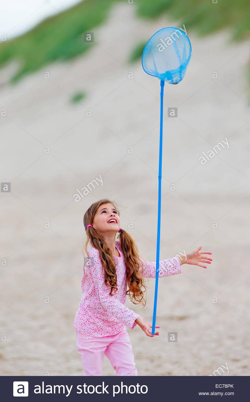 Mädchen ausgleichende Schmetterlingsnetz auf Finger am Strand Stockbild