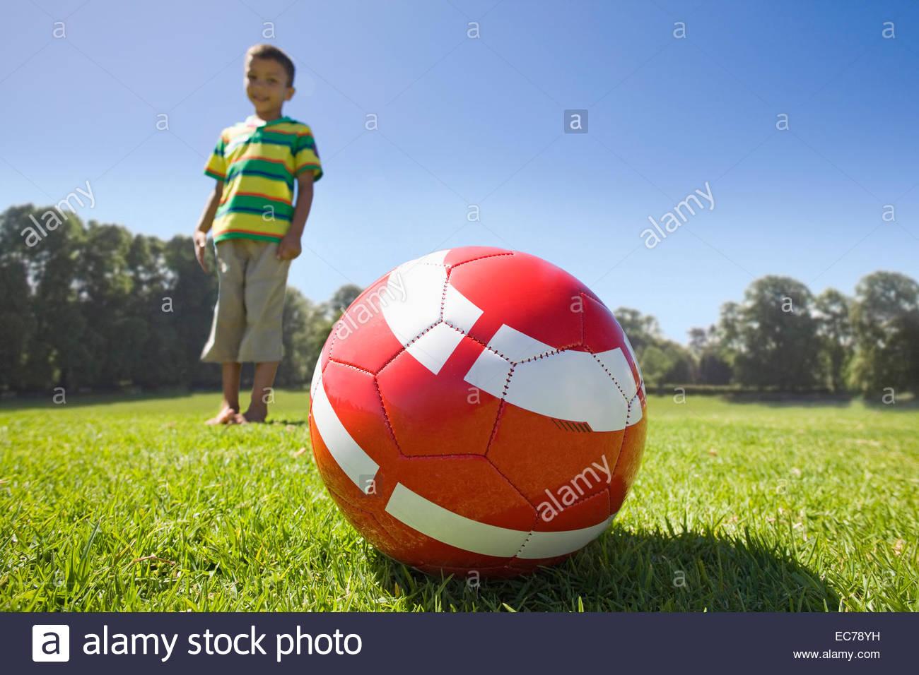 Junge im Park mit dem Fußball Stockbild